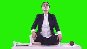 Portrait of young business woman in the office. She sat on the Desk in the Lotus position and meditating in a business stock video footage