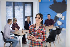 Portrait of young business woman at office with team in backgrou Royalty Free Stock Image