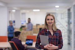 Portrait of young business woman at office with team in backgrou Stock Images