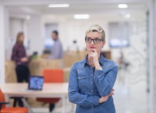Portrait of young business woman at office with team in backgrou Stock Image