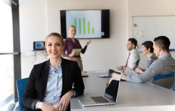 Portrait of young business woman at office with team on meeting Royalty Free Stock Photos