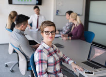 Portrait of young business woman at office with team on meeting Royalty Free Stock Photo