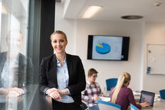 Portrait of young business woman at office with team on meeting Royalty Free Stock Photography