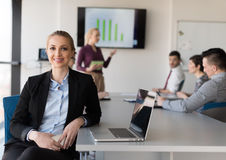 Portrait of young business woman at office with team on meeting Stock Images