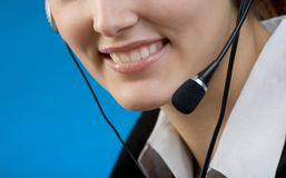 Portrait of young business woman or secretary with headset Royalty Free Stock Photography