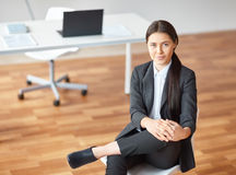 Portrait of young business woman sitting on chair Stock Photos