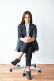 Portrait of young business woman sitting on chair stock images