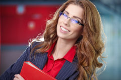 Portrait of a young business woman smiling, in an office en Royalty Free Stock Photos