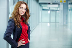 Portrait of a young business woman smiling, in an office en Stock Photo