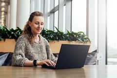Portrait of young business woman in trendy glasses sitting in cafe,working on laptop.Blogger communicates with followers. Portrait of young business woman in stock image