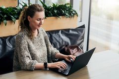 Portrait of young business woman in trendy glasses sitting in cafe,working on laptop.Blogger communicates with followers. Portrait of young business woman in stock images