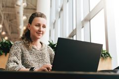Portrait of young business woman in trendy glasses sitting in cafe,working on laptop.Blogger communicates with followers. Portrait of young business woman in royalty free stock images