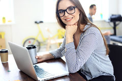 Portrait of a young business woman using laptop. Portrait of a young business women using laptop at office Royalty Free Stock Photos