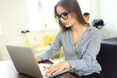 Portrait of a young business woman using laptop. Portrait of a young business women using laptop at office Royalty Free Stock Image
