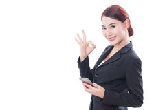 Portrait of young business woman using a mobile phone and showing ok sign Stock Photography
