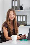 Portrait of young business woman working at her office. Royalty Free Stock Photo