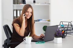 Portrait of young business woman working at her office. Royalty Free Stock Image
