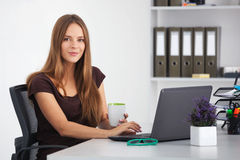 Portrait of young business woman working at her office. Stock Photos