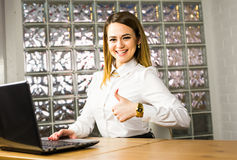 Portrait young business woman working in a modern office. Thumb up. Stock Images