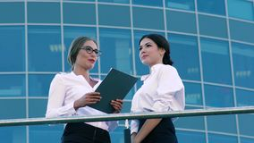 Portrait of young business women talking about their business. Portrait of attractive young business women talking about their business They stand against blue stock footage