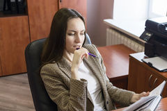 Portrait of young business women, thinking with pen and notepad in office. On a leather armchair stock image