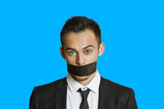 Portrait of a young businessman with adhesive tape on mouth over colored background Royalty Free Stock Image