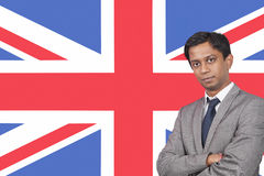 Portrait of young businessman with arms crossed over British flag Stock Photography