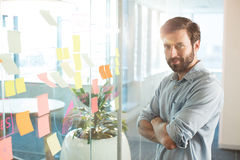 Portrait of young businessman with arms crossed standing at office Stock Photo