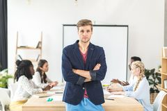 portrait of young businessman with arms crossed standing at table during conference royalty free stock photo
