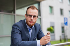 Portrait of young businessman with beard standing in front of of Royalty Free Stock Image