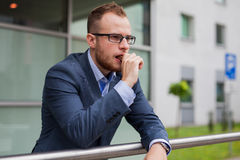 Portrait of young businessman with beard standing in front of of Royalty Free Stock Photo
