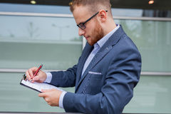 Portrait of young businessman with beard standing in front of of Stock Photo