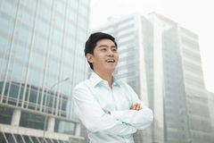 Portrait of young businessman in button down shirt with arms crossed, outdoors, Beijing Royalty Free Stock Image