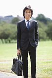 Portrait of young businessman carrying briefcase standing at park Stock Images