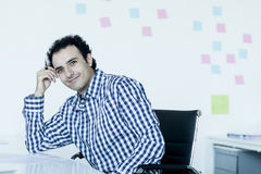 Portrait of young businessman in a checkered shirt at his desk Stock Photo