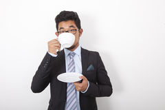 Portrait of young businessman drinking coffee over white background Royalty Free Stock Images