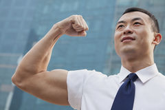 Portrait of young businessman flexing muscle outdoors Stock Photos