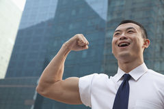 Portrait of young businessman flexing muscle outdoors Royalty Free Stock Photo