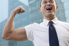 Portrait of young businessman flexing muscle outdoors Royalty Free Stock Image