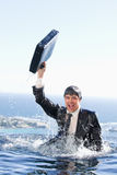 Portrait of a young businessman going out of the water with a br Stock Photography