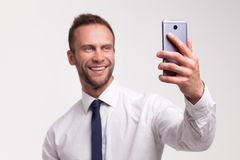 Portrait of young businessman. Portrait of young handsome smiling businessman speaking to cellphone isolated on white studio background royalty free stock images