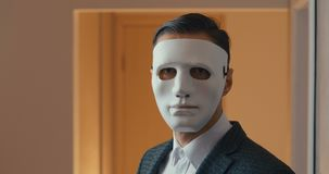 Portrait of young businessman hiding his face with a mask. stock video