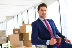Portrait of young businessman holding coffee cup with moving boxes in background at office.  stock photo