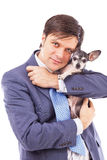 Portrait of a young businessman holding a cute chihuahua dog Stock Image