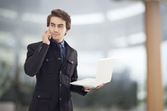 Portrait of young businessman holding laptop Royalty Free Stock Images