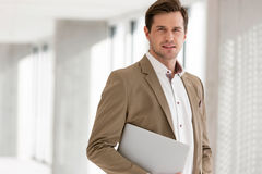 Portrait of young businessman holding laptop in new office Royalty Free Stock Photos