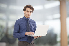 Portrait of young businessman holding laptop Royalty Free Stock Image