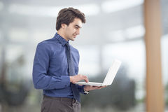 Portrait of young businessman holding laptop Stock Photography