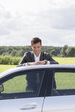 Portrait of young businessman leaning on broken down car at countryside Stock Photo