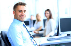 Portrait of young businessman in office with colleagues Stock Photos